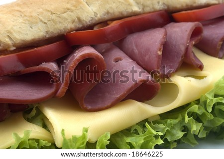 close up of beef and cheese sandwich with lettuce in a nice, soft, small baguette on white background