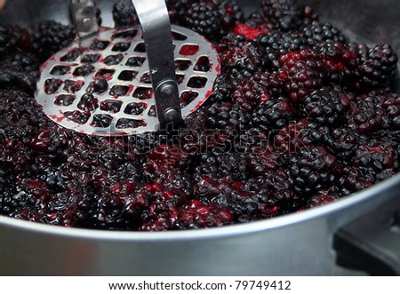 Close up of berries being mashed for jam - stock photo