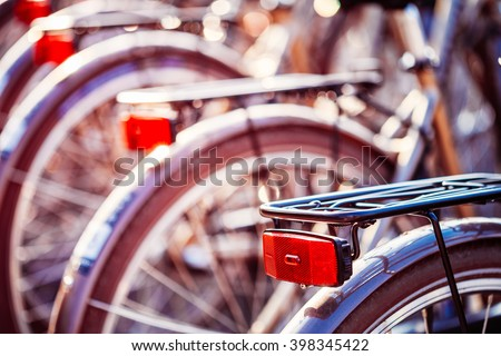 Close Up Of Bicycles On Parking In European City. Sunlight Sunshine Through Spokes Of Wheel. Close Up Of Bike Red Light, Lamp In Bokeh Background.
