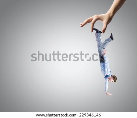 Close up of big human hand catching businessman - stock photo