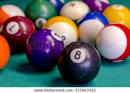 Close up of billiard balls sitting on pool table with eight ball in front - stock photo