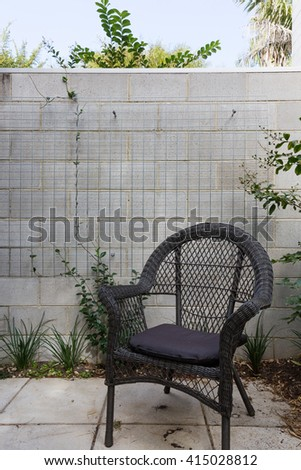 Close up of black cane outdoor chair in courtyard against block brick wall with crepper plant - stock photo