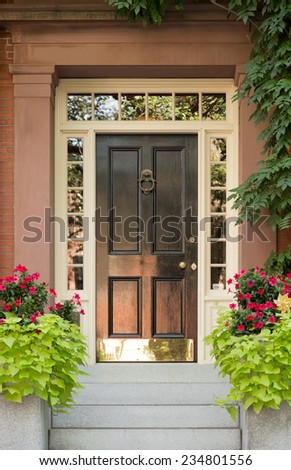 Close Up of Black Door with Surrounding White Door Frame and Windows and Ivy and Potted Plants