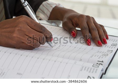 Close-up Of black hands Writing Schedule In Calendar Diary - stock photo