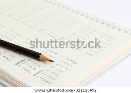 Close up of black sharpened pencil on calendar. - stock photo
