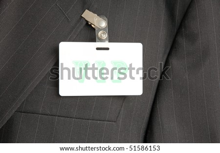 close up of black suit with VIP id card - stock photo