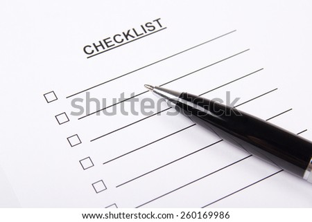 close up of blank checklist and metal pen - stock photo