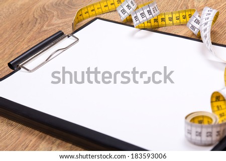 close up of blank clipboard and measure tape on wooden table - stock photo