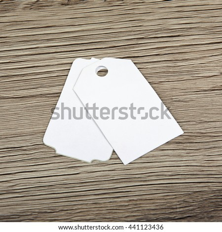 Close up of blank paper tags on wooden surface