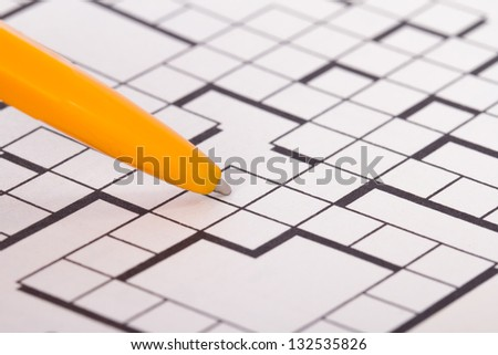 Close up of blank square crossword puzzle for solution with pen. - stock photo
