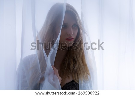 Close-up of blonde sensual woman behind the curtain - stock photo