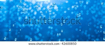 Close up of blue air bubbles in water - stock photo