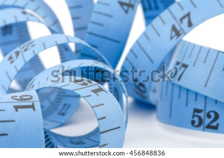Close up of blue measuring tape for health concept, isolated on white background