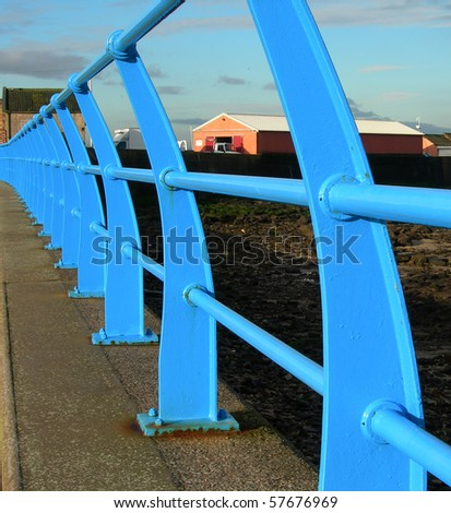 close up of blue painted railings along side the promenade at the seaside