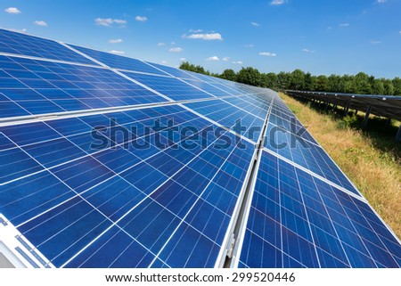 Close up of blue solar panels on ground in long straight line - stock photo