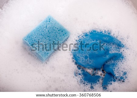 Close up of blue sponge and rag in kitchen sink full of foam - stock photo