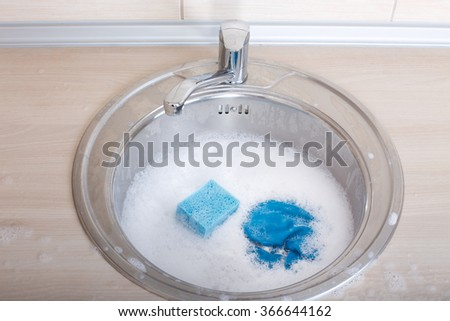 Close up of blue sponge and rag in kitchen sink full of foam