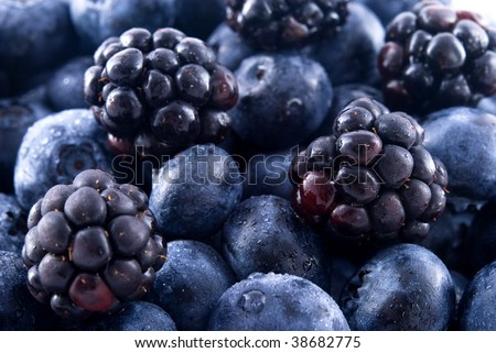 Close up of blueberries and blackberries in a pile - stock photo