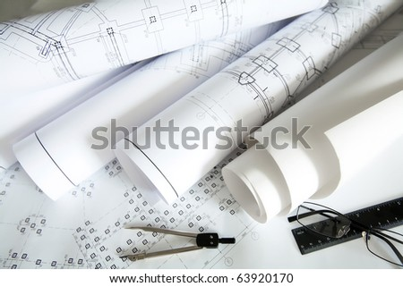 Close-up of blueprints with sketches of projects, eyeglasses and mechanical tools - stock photo
