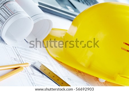 Close-up of blueprints with sketches of projects, helmet and some mechanical tools - stock photo
