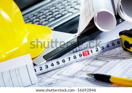 Close-up of blueprints with sketches of projects, laptop, helmet and some mechanical tools - stock photo