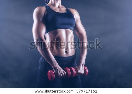 Close up of body fitness girl with dumbbells on a dark background