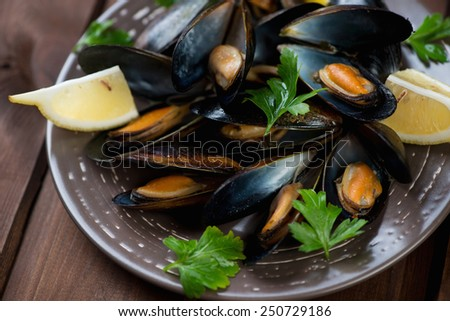 Close-up of boiled mussels with lemon and fresh parsley - stock photo