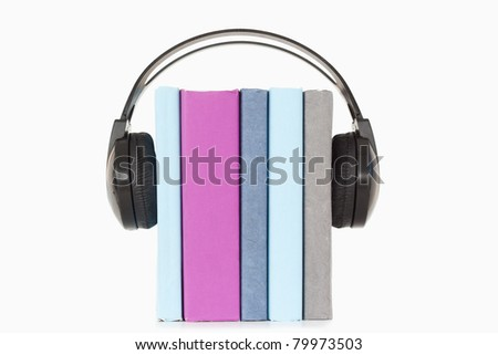Close up of books and headphones against a white background - stock photo