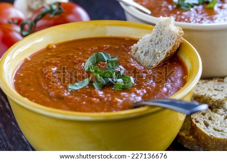 Close up of 2 bowls of homemade tomato basil soup with spoons sitting on wooden table with tomatoes, garlic and slices of whole grain bread - stock photo