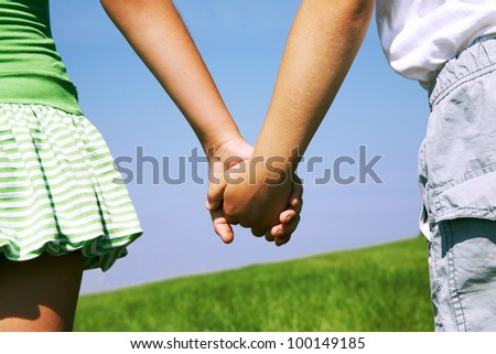 Close-up of boy and girl holding by hands each other