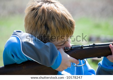 Close up of boy pulling trigger on rifle - stock photo