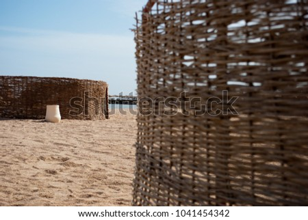 Close up of braided wind protection on sand beach. Closeup of non focus rattan weaved protection with white ceramic pot. Sunny sand beach and rattan wind protection
