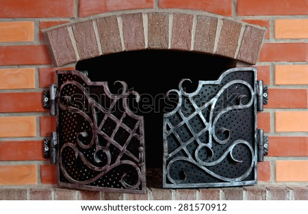 Close up of brick fireplace with an iron gate - stock photo