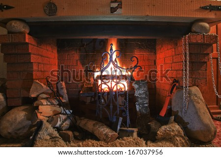 Close-up of brick fireplace with an iron gate with a bright flame burning logs