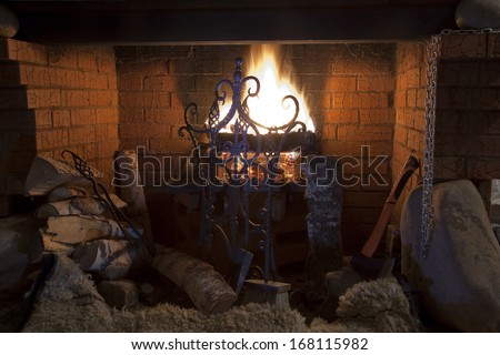 Close-up of brick fireplace with an iron gate with a bright flame burning logs - stock photo