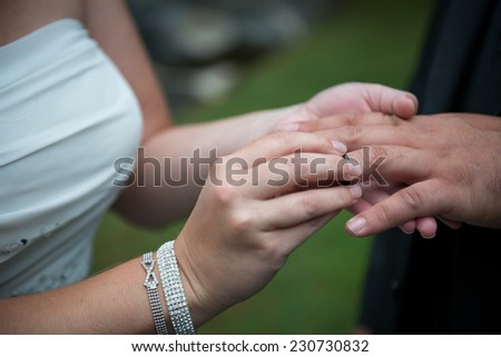 Close up of bride and groom exchanging wedding vows and rings - stock photo