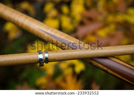 Close up of bride and groom's wedding rings on pool cues with rustic background - stock photo