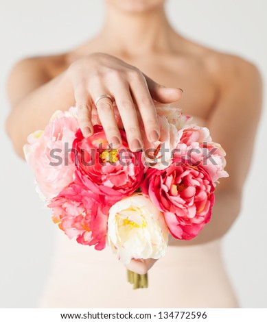 close up of bride with bouquet of flowers and wedding ring. - stock photo