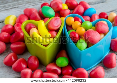 Close-up of bright colorful candies in heart shaped baking forms - stock photo