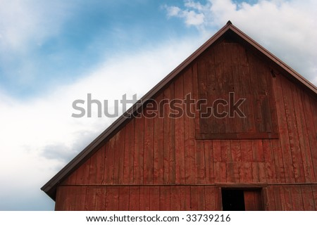 Close-up of bright red barn roof against cloudy blue sky - stock photo
