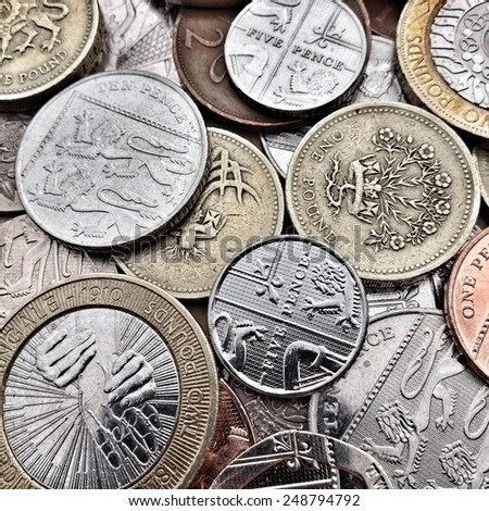 Close up of British Coins including bronze and silver, pound coins, pence and pennies. Creative filters and textures have been applied for effect - stock photo