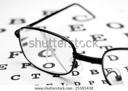close up of broken glasses and snellen chart - stock photo
