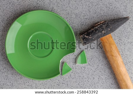 close up of broken hammer green plate on grey background - stock photo