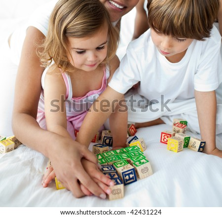 Close-up of brother and sister playing with cube toys on the bed - stock photo