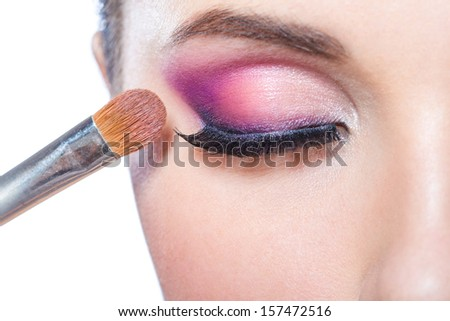 Close up of brush applying bright pink makeup on eye of pretty girl, isolated on white - stock photo