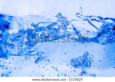 Close-up of bubbled water with soft blue background freezed in motion - stock photo