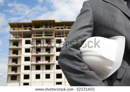 Close-up of builder holding helmet with construction at background - stock photo