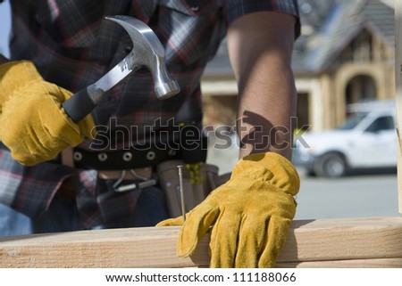 Close-up of builder's hands hammering a nail into wood - stock photo
