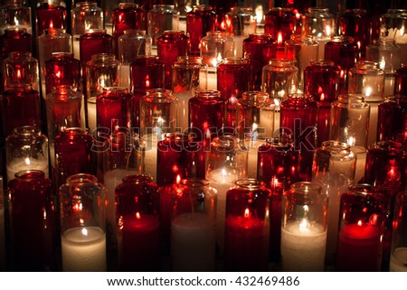 close up of burning candles in long, white and red transparent chandeliers in a church setting - stock photo