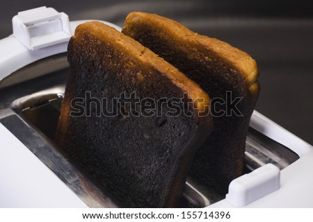 Close-up of burnt toasts in toaster - stock photo